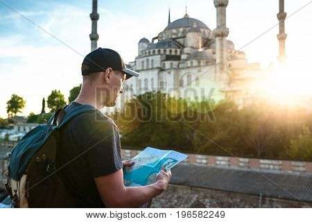 A traveler in a baseball cap with a backpack is looking at the map next to the blue mosque - the famous sight of Istanbul. Travel, sightseeing.