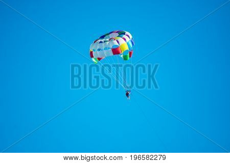Parasailor on multi-colored parachute flying in blue clear sky sunny weather inspirational summer vacations freedom