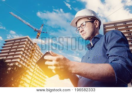 builder is a man in a protective helmet and a tablet computer in the hands of a crane, a multi-storey house. Concept construction, business, technology