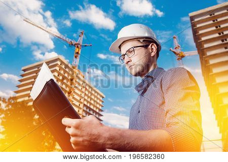 close-up man construction builder worker - foreman is engineer in protective helmet, glasses on the background of building house with crane. Concept calculation construction time, cost.
