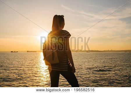 A young tourist girl with a backpack stands next to the sea at sunset and looks into the distance. Relaxation, travel, vacation.