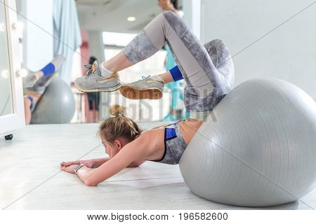Fit young woman doing stretching exercise for back on fitness ball lying trying to reach head with feet in sports club.