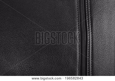 Black leather texture of the bag; Buttoned zipper close-up