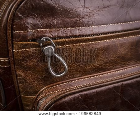 Buttoned zipper on a leather bag for men; Slider