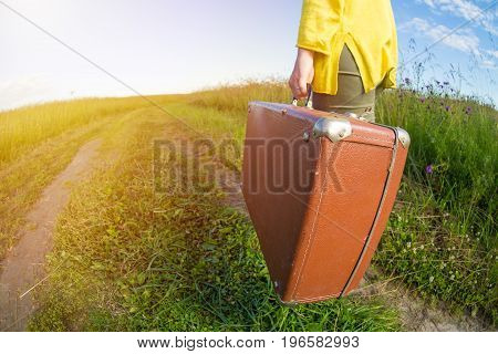 Young woman carries brown vintage suitcase in the field road during summer sunset. Travel concept