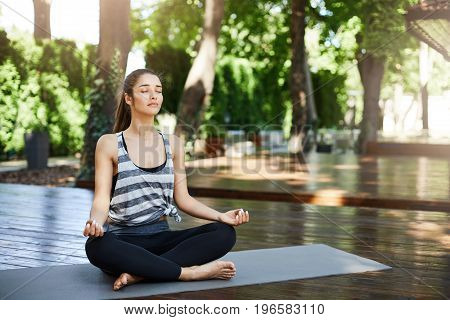 Gorgeous girl meditating in the middle of yoga temple breathing deep with closed eyes. Basic practice.