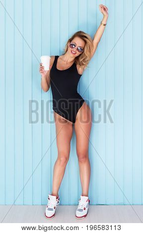 Beauty woman portrait with hand up Beautiful girl in bodysuit holding cup of coffee take away.