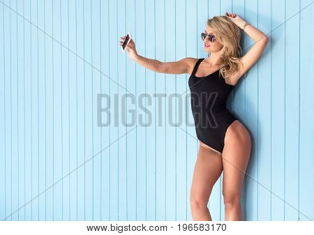blonde woman in bodysuit with perfect body taking selfie with smartphone.