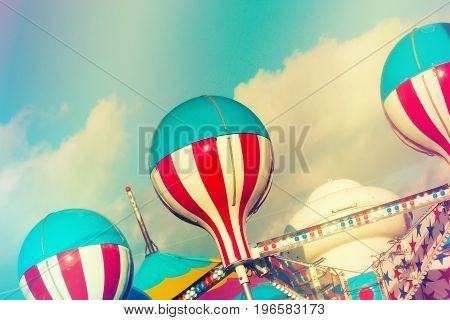 Bright, fun and festive carnival ride abstract photography with blue sky and clouds in background.