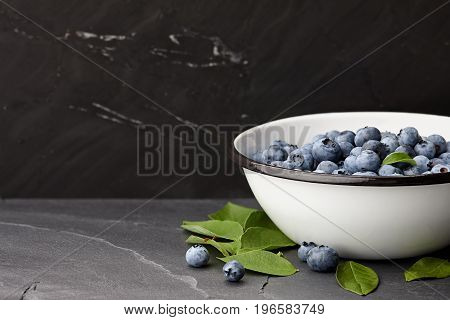 Fresh ripe blueberries with leaves bowl on black stone countertop