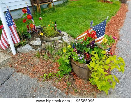 Flags, flowers, and ivy planted in wooden barrels