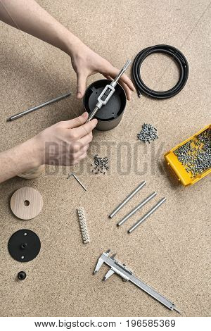 Man is using a t-wrench on a black metal cylinder on the light table. On the table there are billets, cable, plastic box with screws, tools, caliper, bushings, connector. Closeup. Vertical.