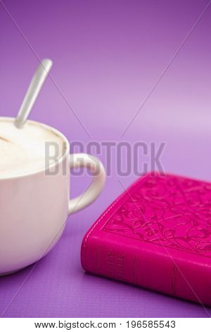 Closed Pink Bible on a Purple Background with a Cup of Coffee