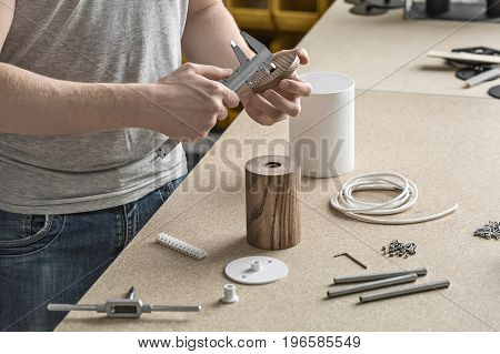 Specialist is using a caliper on the round wooden detail in the workshop. On the table there are wooden and metal cylindrical billets, cable, connector, screws, t-wrench, bushings. Closeup.