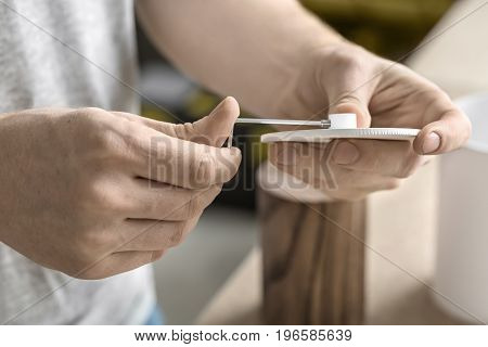 Guy is using a wrench on the round metal white detail in the workshop. On the table there are wooden and white metal cylindrical billets. Closeup low apeture photo. Horizontal.