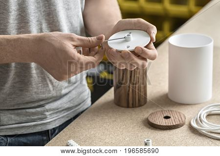 Man is using a wrench on the round metal white detail in the workshop. On the table there are wooden and white metal cylindrical billets, cable. Closeup. Horizontal.