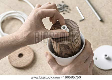Assembly of the lamp in the workshop. Man is putting a white detail on the cylindrical wooden part which is in the metal white billet. Other tools are on the table under his hands. Closeup.