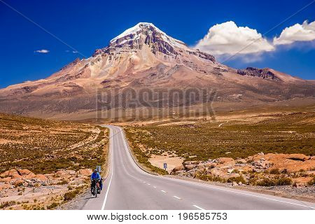 Female solo cyclist riding on bicycle on the beautiful road through Nevado Sajama National Park, Bolivia, South America