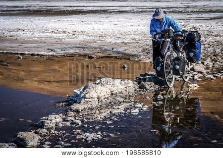 Lonely female cyclist travelling through the biggest salar in the world, Salar de Uyuni in Bolivia