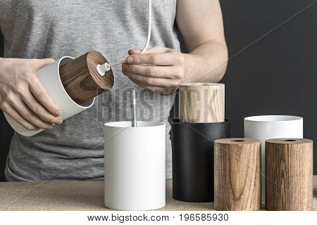 Lamp assembling in the workshop. Man holds a white lamp with a wooden part per the cable. On the table there are other lamp billets. Indoors. Closeup. Horizontal.