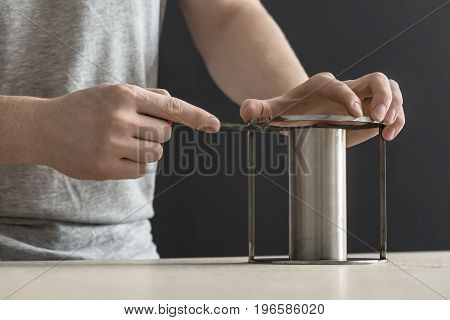 Steel cylindrical construction under the hand of the man on the table in the workshop on the dark background. Guy is using a rasp on it. Closeup photo. Horizontal.