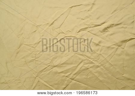 Crumpled yellow fabric background. Dented tissue texture.