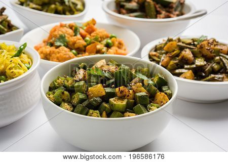 group photo of indian popular green vegetable food curries or sabzi or sabji like cauliflower/phool gobi, bhindi or okra, gawar or cluster beans, french beans, cabbage or patta gobi, flat green beans