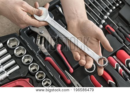 Dark toolbox on the light tabletop in the workshop. Man holds a spanner above it. Inside the toolbox there are black-red wrenches, screwdrivers, spanners and different nozzles. Closeup. Horizontal.