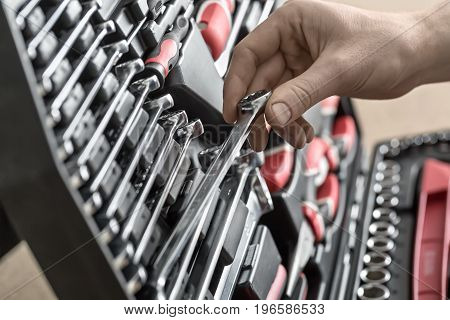 Male hand holds a spanner above the black toolbox. Inside it there are black-red pliers and screwdrivers, spanners and different nozzles. Closeup photo. Horizontal. poster