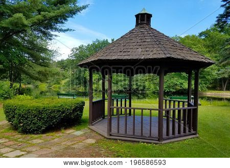 Gazebo in the park with benches and a river in the background