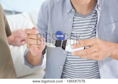 Young male volunteer giving medicine to senior man, closeup