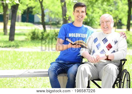 Young male volunteer reading book to senior man on wheelchair outdoors