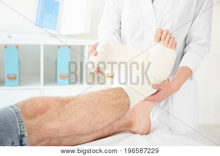 Doctor applying bandage onto patient's leg in clinic