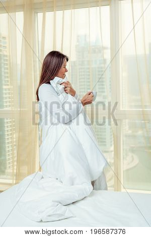 Mature woman is standing by the window in her bedroom in a hotel/apartment