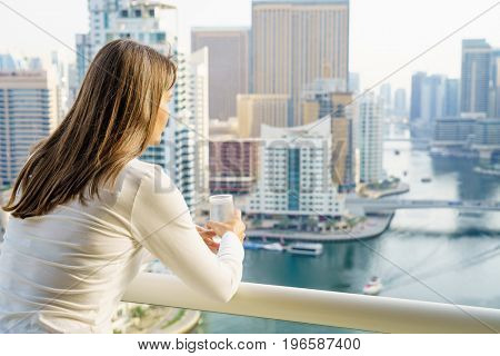 Mature woman is enjoying city view from her balcony in highrise building.
