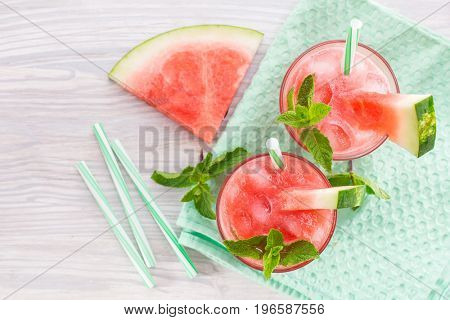 Summer cold drink with watermelon, mint and lemon on a wooden background. view from above