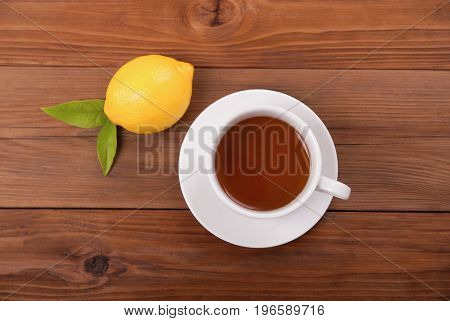 Cup of tea and lemon with leaves on a wooden background. View from above .