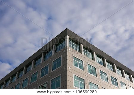 Cloudy sky with illuminated reflected glass facade on modern office building