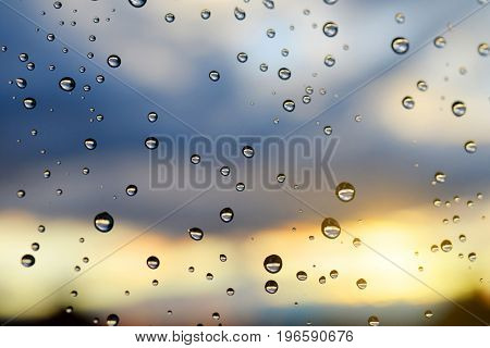 Water drops on a window glass after the rain at sunset.