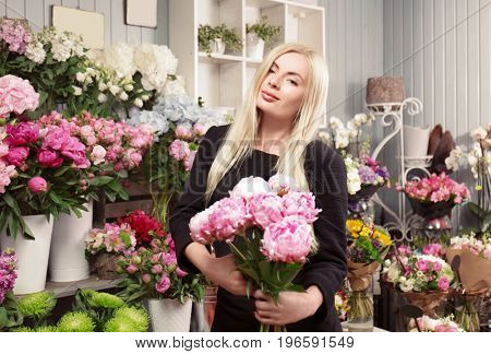 Young woman holding beautiful peonies in flower shop