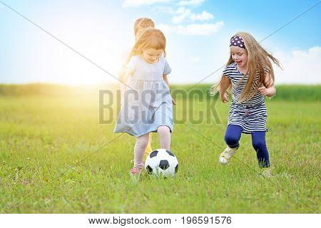 Cute little girls playing football on green grass