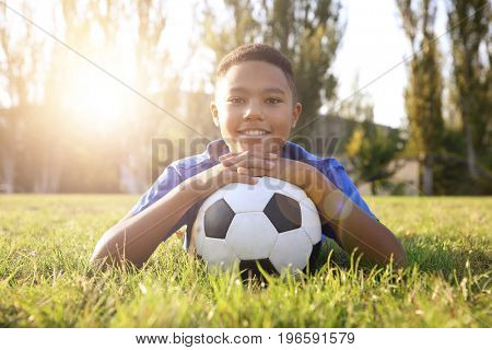 African-American boy with soccer ball lying on green grass in park. Football concept