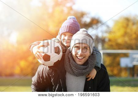 Father and son with ball on football field