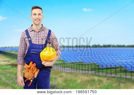 Young engineer and solar panels on background