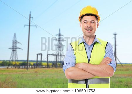 Engineer and electric substation on background
