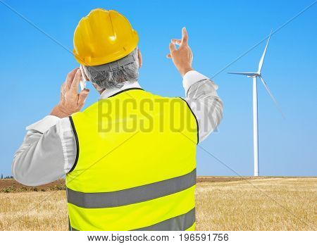 Senior engineer talking by phone and wind turbine on background