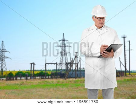Senior engineer with clipboard and electric substation on background