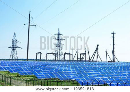 Solar panels and electrical transmission towers in field. Concept of eco friendly thechnology