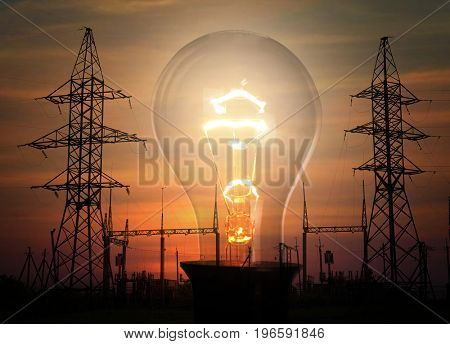 Electrical transmission towers, substation and light bulb on sky background at sunset