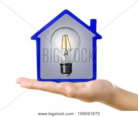 Woman holding model of house and light bulb on white background. Concept of energy consumption